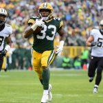 Oct 22, 2017; Green Bay, WI, USA;  Green Bay Packers running back Aaron Jones (33) runs past New Orleans Saints center Zach Wood (49) for a touchdown in the first quarter at Lambeau Field. Mandatory Credit: Benny Sieu-USA TODAY Sports