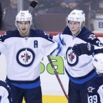 Winnipeg Jets' Nikolaj Ehlers, of Denmark, from left to right, Mark Scheifele, Patrik Laine, of Finland, and Toby Enstrom, of Sweden, celebrate Laine's goal against the Vancouver Canucks during the second period of an NHL hockey game in Vancouver, B.C., on Thursday December 22, 2016. THE CANADIAN PRESS/Darryl Dyck